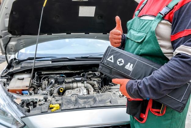 Publicité de service de voiture. mécanicien debout près de la voiture montrant le pouce vers le haut. voiture avec capot ouvert