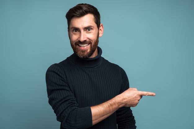 Publier ici. homme barbu positif pointant le doigt vers l'extérieur en prêtant attention à l'espace vide pour la publicité, en regardant la caméra avec un sourire à pleines dents. studio intérieur tourné isolé sur fond bleu