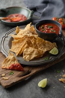 Puce de nachos mexicain avec des sauces de salsa tomate en plaque sur une table en bois et pierre