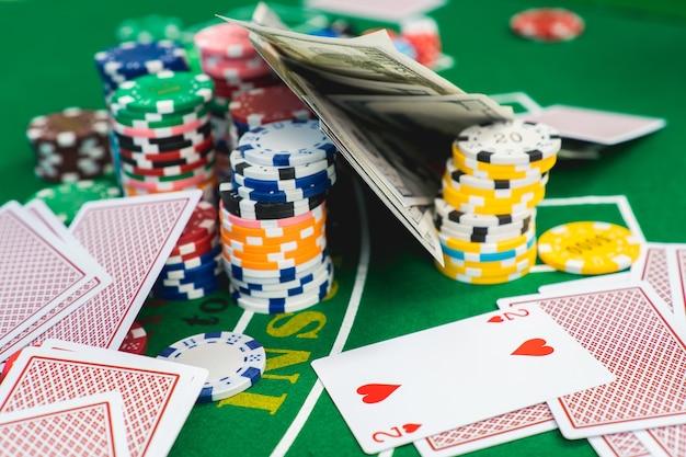 Puces et cartes pour le poker en main sur la table verte