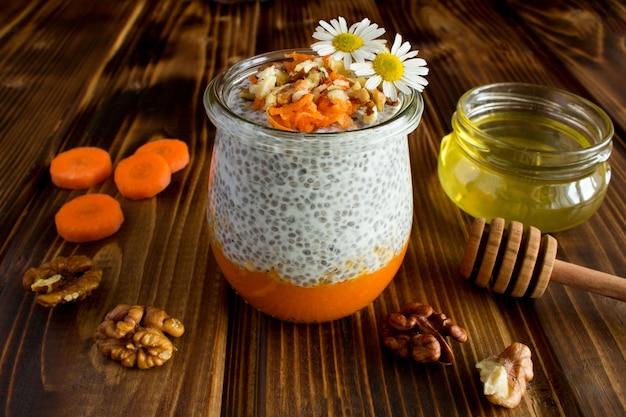 Pudding au chia, aux carottes, aux noix et au miel sur le fond en bois marron