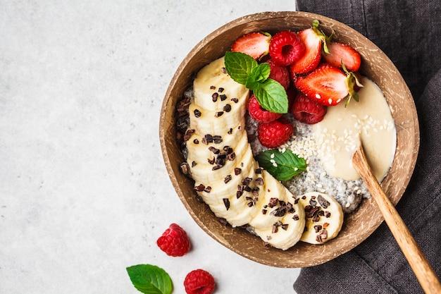 Pudding au chia avec baies, banane, beurre de cacahuète et éclats de cacao dans un bol de noix de coco