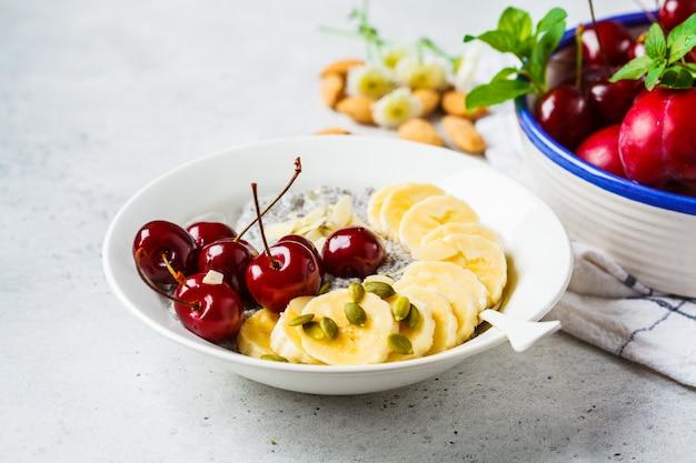 Pudding au chia avec banane, cerise et noix dans une assiette blanche.