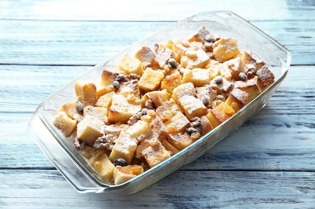 Pudding au pain aux raisins secs, noix et sucre en poudre dans un plat allant au four sur la table