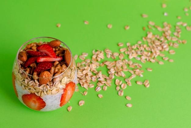Pudding au yogourt avec fraises fraîches, avoine et noix dans un verre sur vert