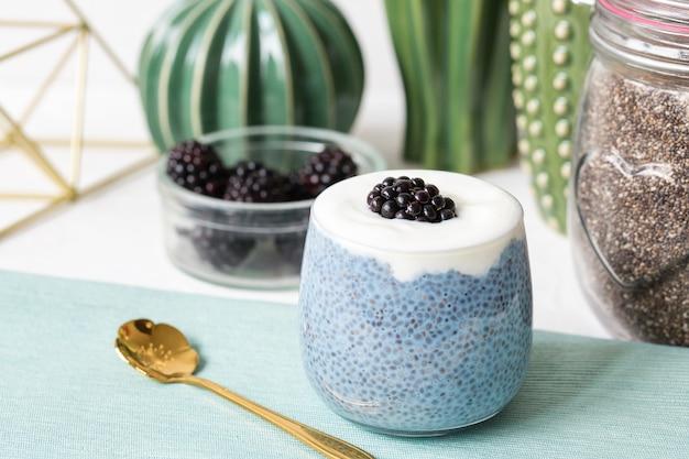 Pudding aux graines de chia bleu avec des mûres dans un verre