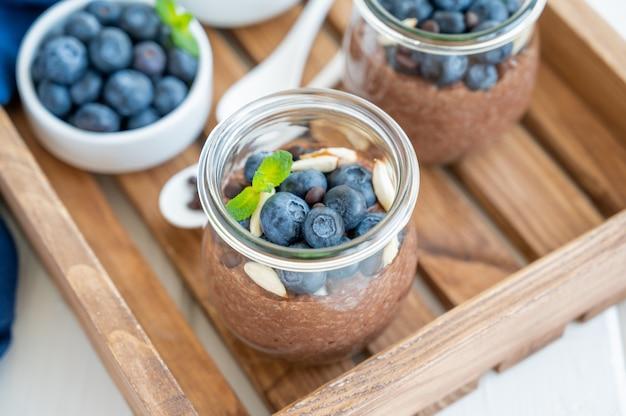 Pudding de chia au chocolat avec amandes aux bleuets et menthe sur le dessus dans un bocal en verre
