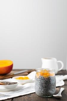 Pudding de chia en pot de verre au lait d'amande et à la mangue sur une table en bois rustique