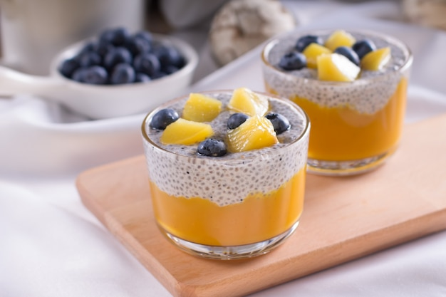 Pudding chia végétarien sain à la vanille dans un verre avec des baies fraîches au lait de coco