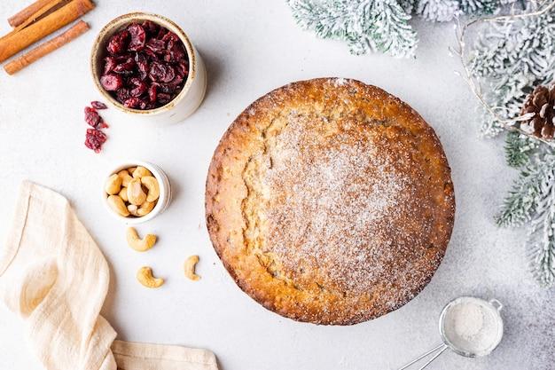 Pudding de gâteau de noël traditionnel avec des fruits et des noix avec fond clair de décorations de noël