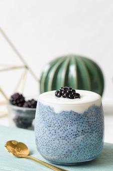 Pudding de graines de chia bleu avec des mûres dans un verre