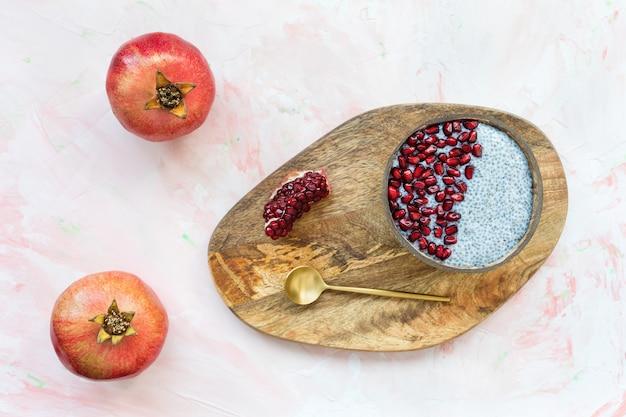 Pudding de graines de chia avec des graines de grenade fraîches dans un bol de noix de coco, une cuillère dorée et des grenades mûres rouges