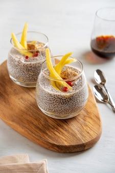 Pudding de noix de coco chia végétalien à la mangue sur fond blanc. nutrition saine, superaliments. vue rapprochée.