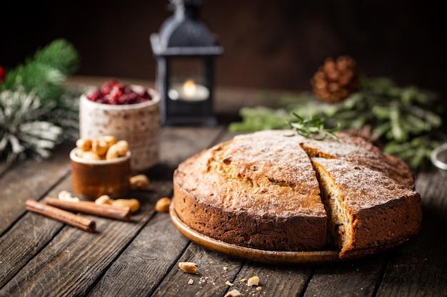 Pudding traditionnel de gâteau de noël avec des fruits et des écrous avec le fond foncé de décorations de noël