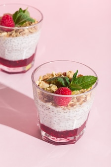 Pudding à la vanille aux graines de chia avec musli d'avoine à la framboise et menthe sur une photo de haute qualité à l'ombre dure rose