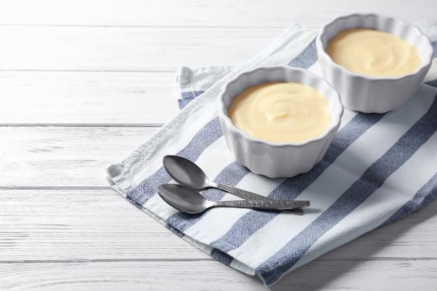Pudding à la vanille dans des bols en céramique sur table en bois blanc