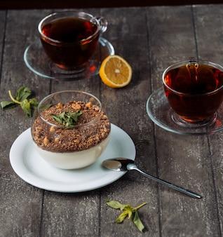 Pudding à la vanille recouvert de miettes de chocolat et de noix, servi avec du thé