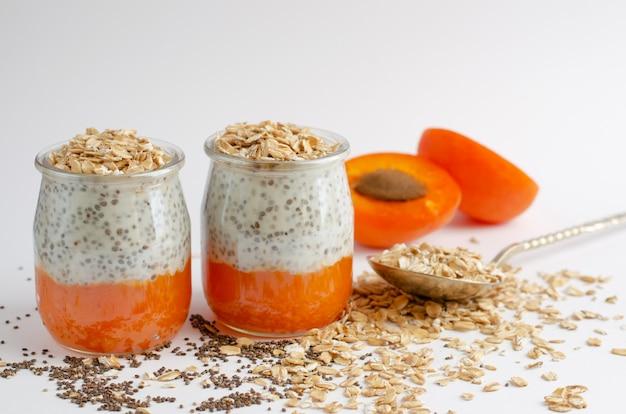 Puddings aux graines de chia avec des plats d'abricots et d'avoine frais sur fond blanc