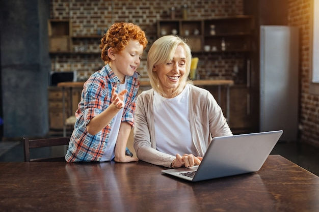 Puis-je essayer. dame senior aimante regardant un écran de son ordinateur portable tout en écoutant son petit-fils aux cheveux bouclés parler d'ordinateurs.