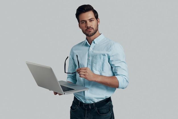 Puis-je vous aider? beau jeune homme utilisant un ordinateur portable en se tenant debout sur fond gris