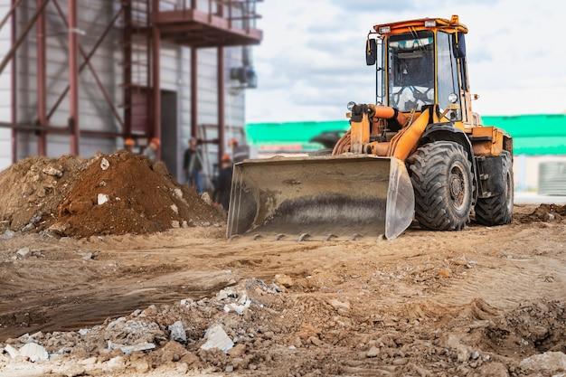 Un puissant chargeur frontal sur le chantier de construction effectue le ponçage. déplacement du sol avec du matériel de construction. les fouilles.