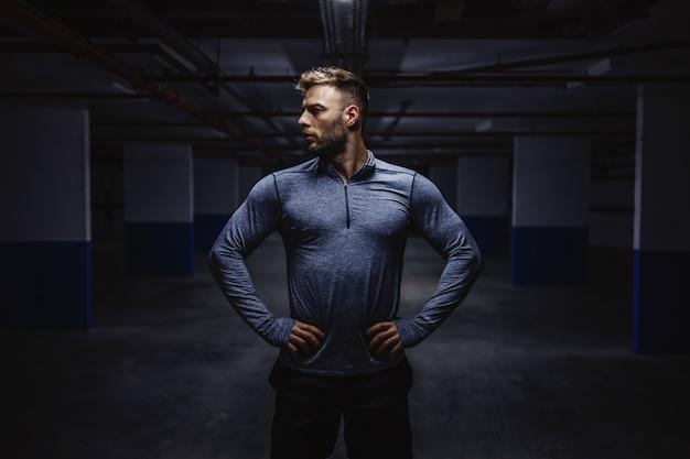 Puissant homme caucasien fort en tenue de sport debout dans le garage avec les mains sur les hanches et en détournant les yeux. la nuit. concept de vie urbaine.