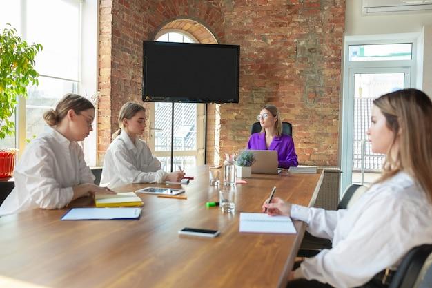 Puissant. jeune femme d'affaires caucasienne dans un bureau moderne avec équipe.