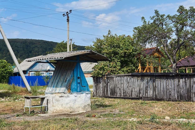 Puits rural communal avec toit en ardoise et treuil à main à la campagne