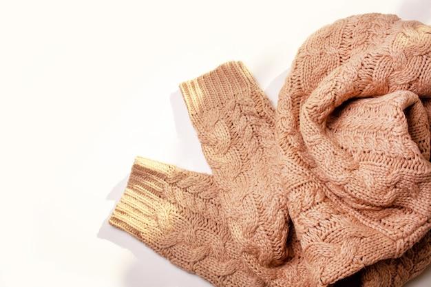 Pull beige tricoté chaud sur une table blanche. vue d'en-haut. notion d'automne