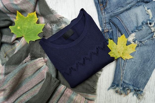 Pull bleu, écharpe, jeans et feuilles d'érable. à la mode
