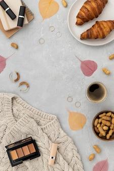Pull, croissants, maquillage, café, rouge à lèvres et plus d'objets en forme de cadre sur fond de béton