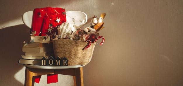 Pull d'hiver posé sur une chaise avec un panier de décorations de noël