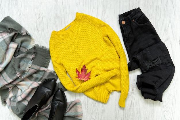 Pull jaune, jean noir et écharpe