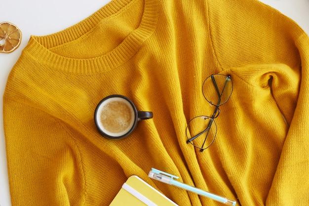 Pull jaune vif avec bloc-notes, stylo, lunettes et une tasse de café