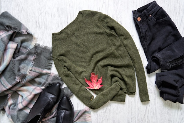 Pull kaki, jean noir et écharpe