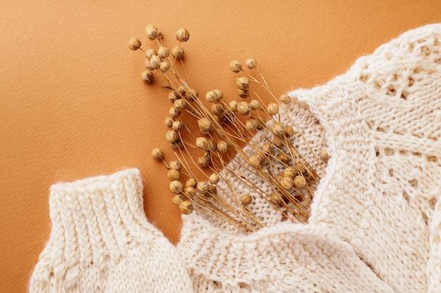 Pull en laine beige tricoté à fleurs sur fond marron clair. collection de mode du concept de vêtements d'automne. conception de mise en page de cardigan créatif. imitation d'une tête humaine avec des fleurs.