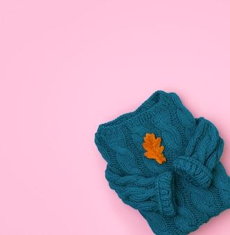 Pull en maille confortable turquoise vue de dessus à plat avec feuille sèche de chêne