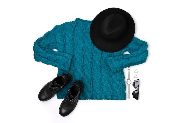 Pull plat turquoise vue de dessus, bottes, lunettes de soleil, montre et chapeau