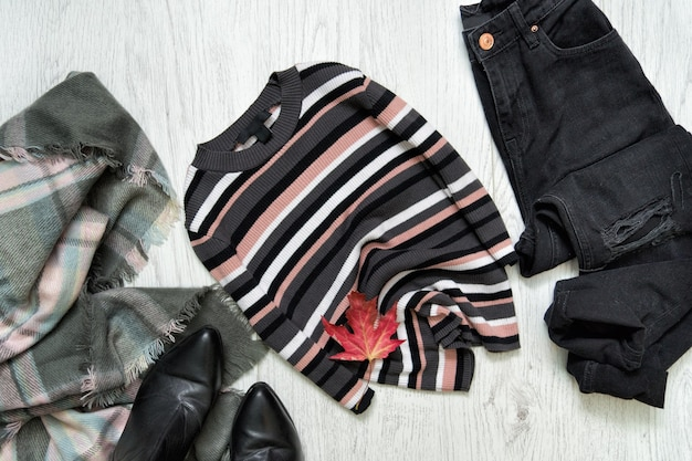 Pull rayé, jean noir et écharpe sur surface en bois