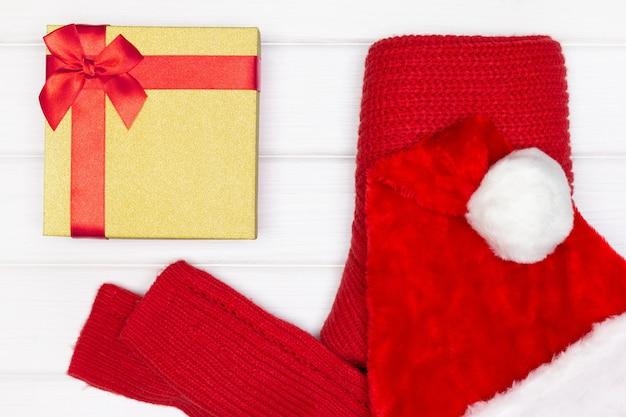 Pull en tricot rouge, bonnet de noel, coffret cadeau sur planches de bois blanc - vue de dessus. concept de cadeau de noël