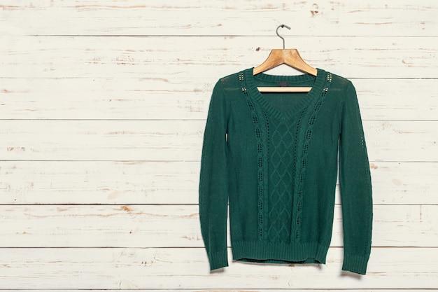 Pull tricoté sur étendoir en bois