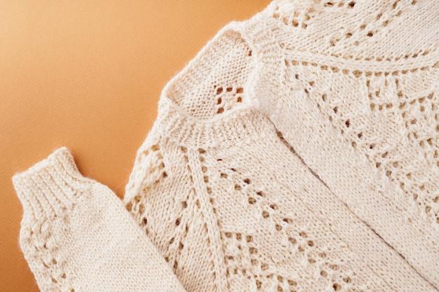 Pull tricoté en laine beige naturelle, gros plan. motifs et détails des produits tricotés. beau pull pour femme à la mode, confortable sur un fond d'automne marron. concept de vêtements d'automne.