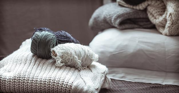 Pull tricoté avec des pelotes de laine, un concept de chaleur et de confort, passe-temps, arrière-plan, gros plan