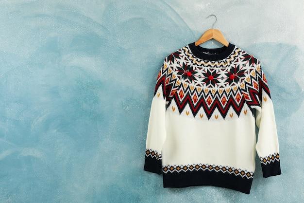 Pull tricoté suspendu à un cintre sur fond bleu