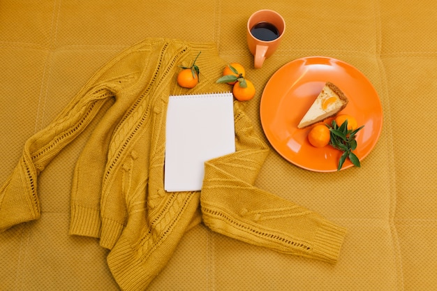 Pull tricoté, tasse de café, cheesecake, mandarines, cahier sur table orange