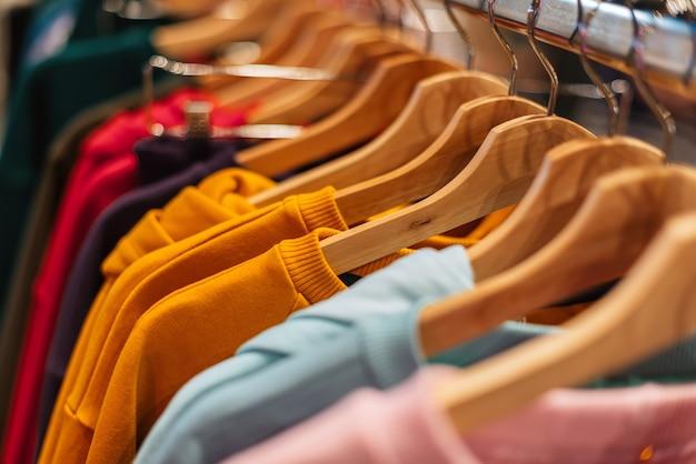 Des pulls en coton multicolores sont suspendus à des cintres dans le magasin.