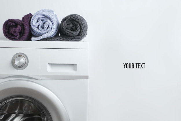 Pulls roulés de couleur sur la machine à laver sur fond blanc avec copie espace