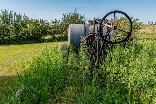 Pulvérisateur agricole vintage entouré de hautes herbes