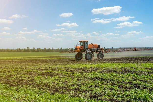 Un pulvérisateur automoteur travaille sur un champ sous un ciel bleu avec des nuages