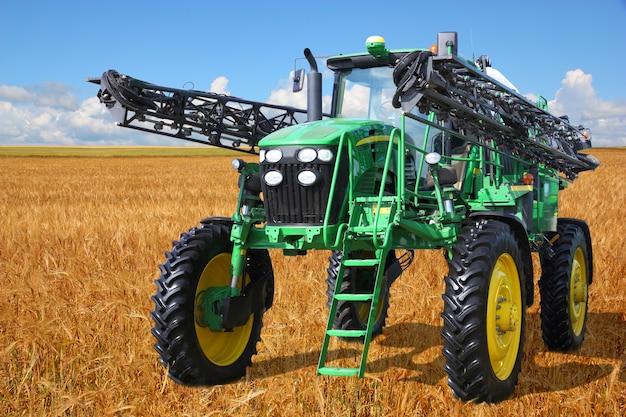 Pulvérisateur tracteur moissonneuse sur un champ de blé avec un ciel bleu